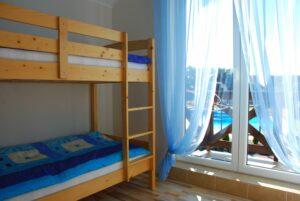 Drugi pokój z łóżkiem piętrowym, balkonem i widokiem na basen i osiedle